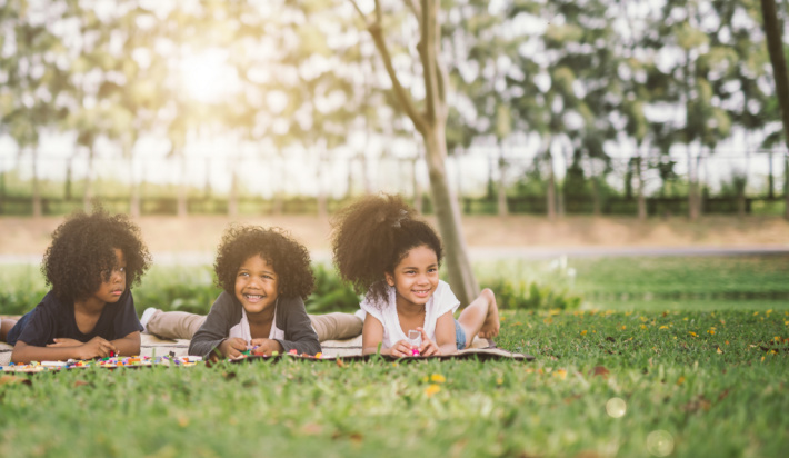 Picnic lunch outside - Kids Activities Blog - three kids outside on a blanket in backyard
