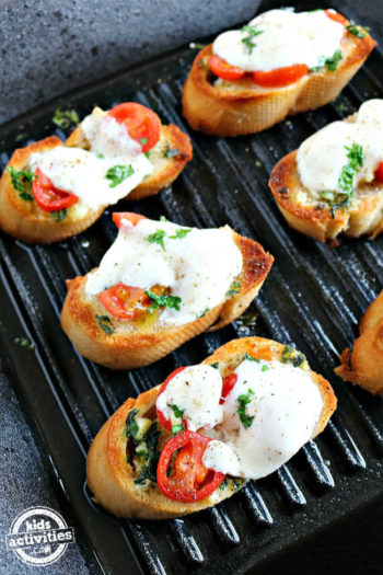Crostini topped with garlic, herbs, and tomato.