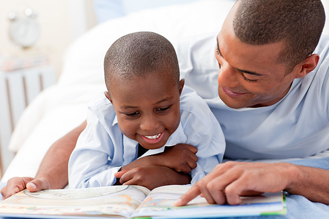 father and child reading a book together