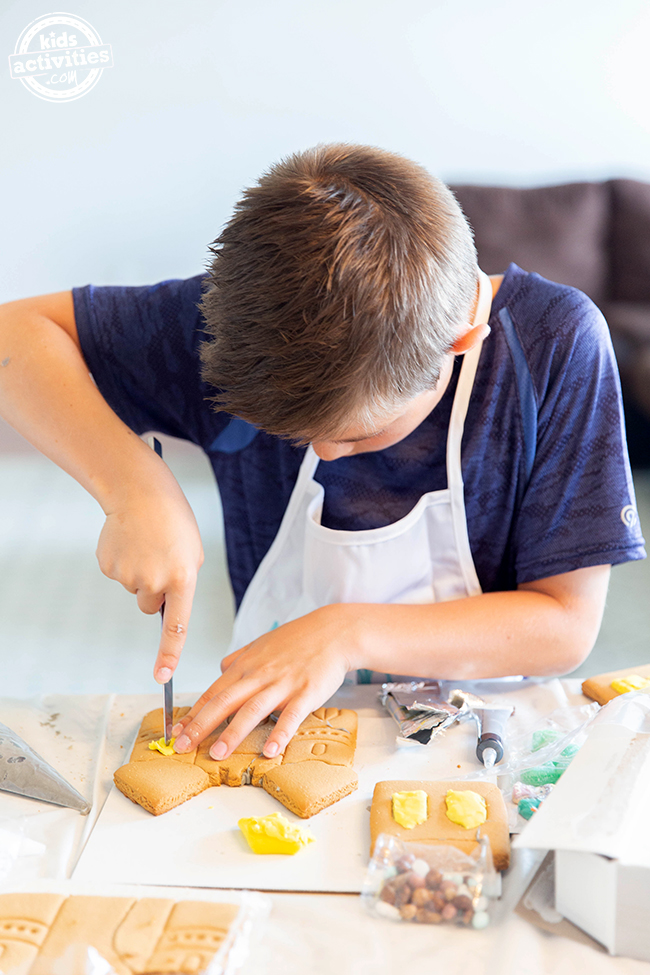 A boy using a nice to cut yellow fondant and putting it on a castle cookie.