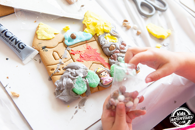 A castle with a mash of sweets on it. It has a yellow roof and a blue roof with a random purple candy in the middle. Red icing is spread across the middle and grey icing on the sides. At the bottom there are green gummy bushes and a sugar princess.