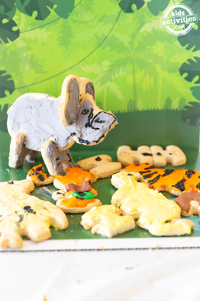 A gray elephant cookie with animals that are broken and laying around with yellow and orange frosting against a jungle background.