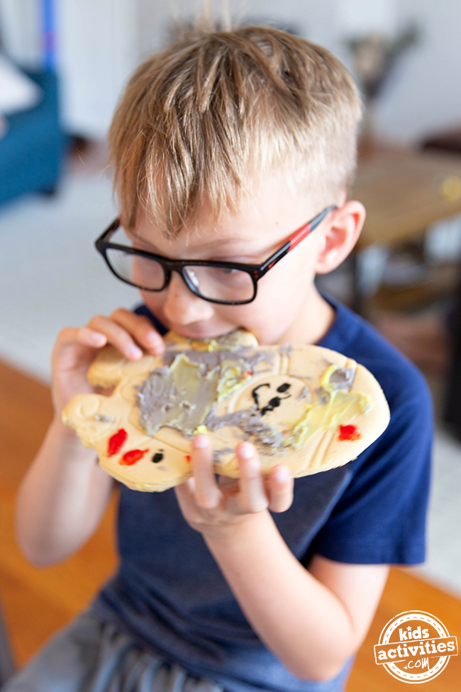 Little boy in glasses eating a spaceship cookie with random frosting spread all over it.