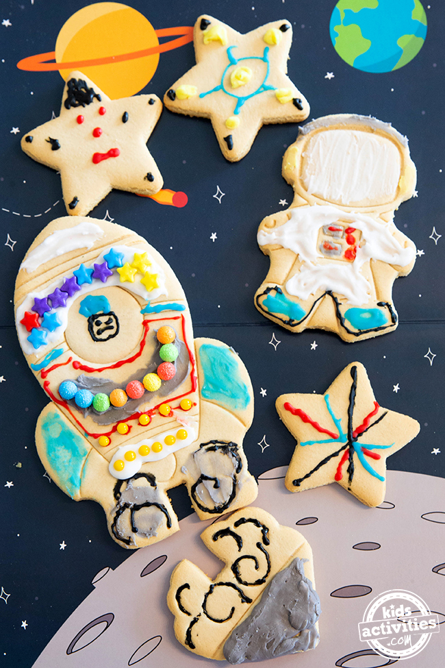 Space cookies against an outer space background. Stars, spaceship, escape pot, and an astronaut.