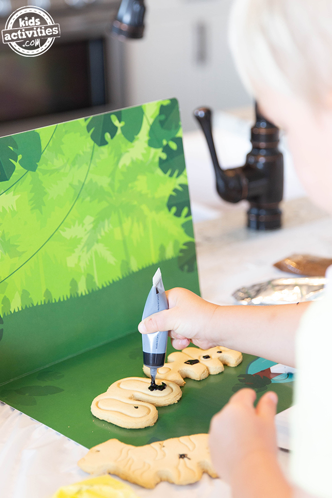 A small boy putting black icing on some unidentified cookie pieces against a jungle cardboard base.