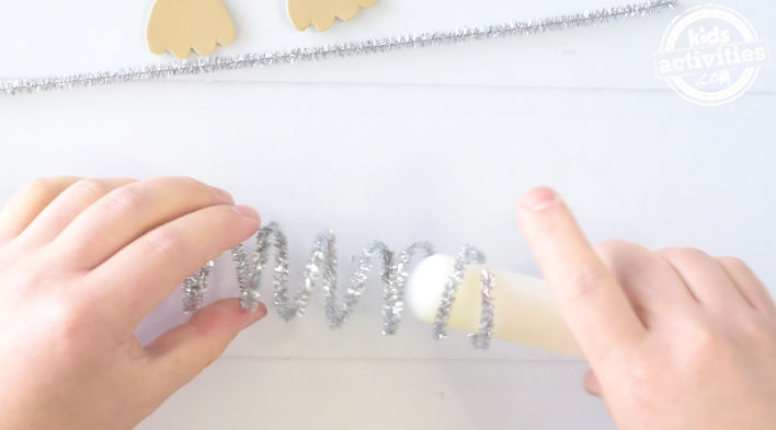 hands wrapping sparkly silver pipe cleaner around a cylinder to create a spiral shape