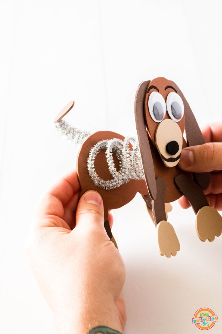 Person putting the back part of Slinky Dog from Toy Story onto the silver coil between his head and tail.