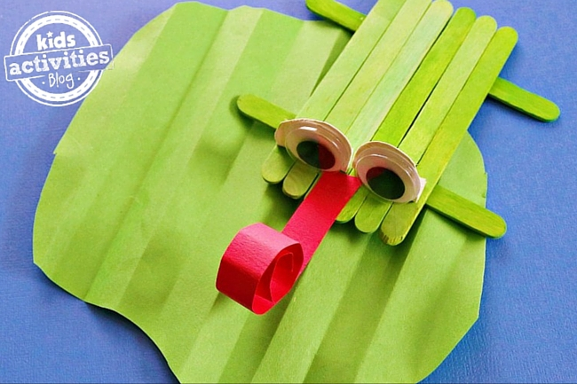 popsicle stick frog craft with craft stick frog sitting on a craft paper lilly pad