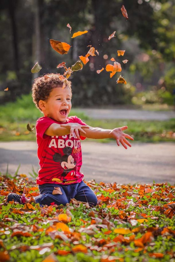 A young boy kneeing on grass and throwing leaves up into the air.