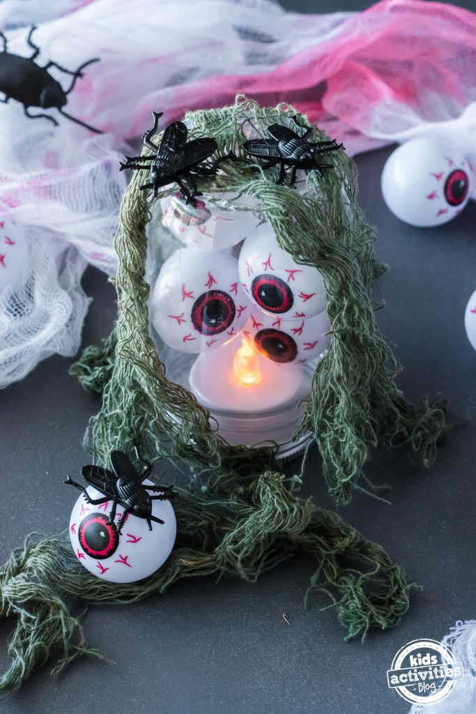 Halloween eyeball decorations like this eyeball lantern is filled with fake eyeballs, has an LED light in it, and covered in green netting and plastic bugs.