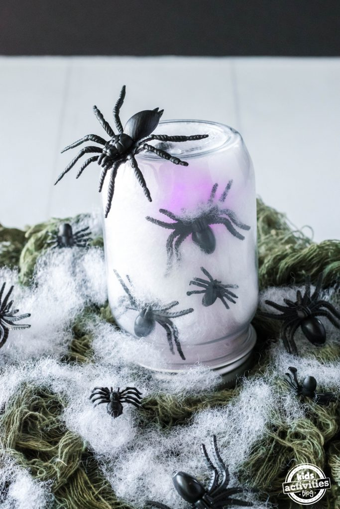 Halloween lantern filled with cotton webs with black plastic spiders in and on it, filled with purple lights.