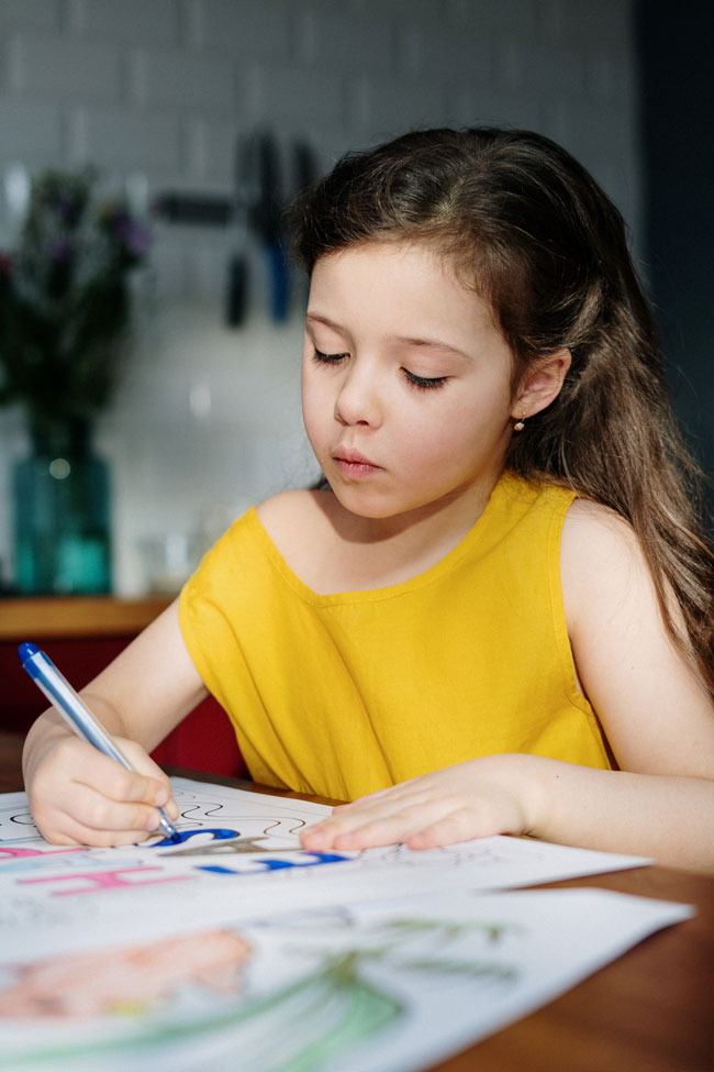 Young girl with a yellow shirt sitting at a table coloring with a blue pen.