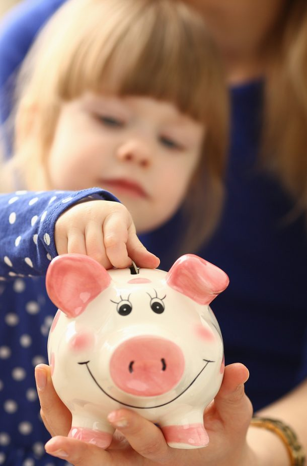 Piggy banks for kids that are pink, ceramic, with a smile with a little girl putting a coin in it.
