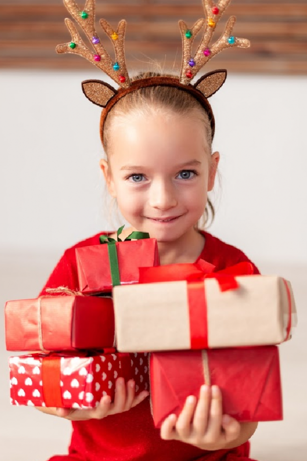 preschooler with reindeer antlers shows new gifts, not yet unwrapped