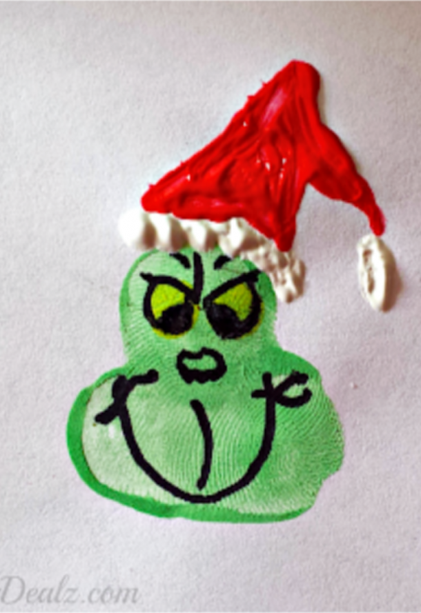 Fingerprint Grinch Christmas craft with a red and white Christmas hat.
