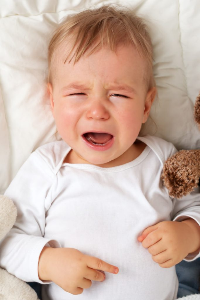 fever stickers can tell if child has fever without waking them up - Kids Activities Blog - baby laying in bed crying