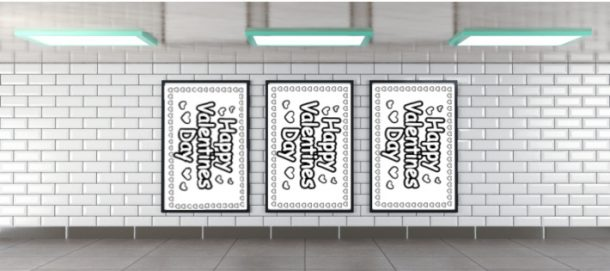 Three Happy Valentines Day posters in a black framed picture framed against a white brick wall.