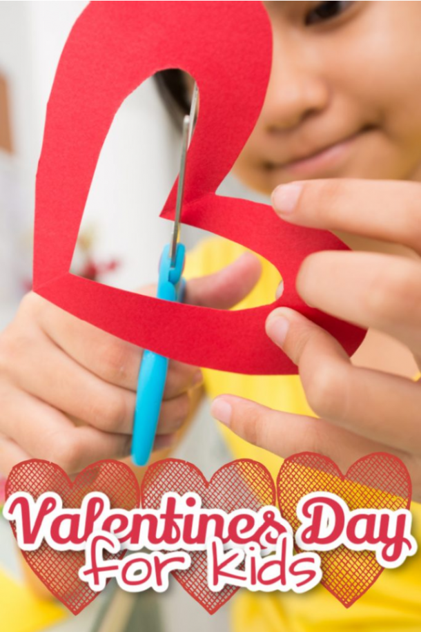 Valentine's activities for kids as a child cuts out a paper heart with blue scissors