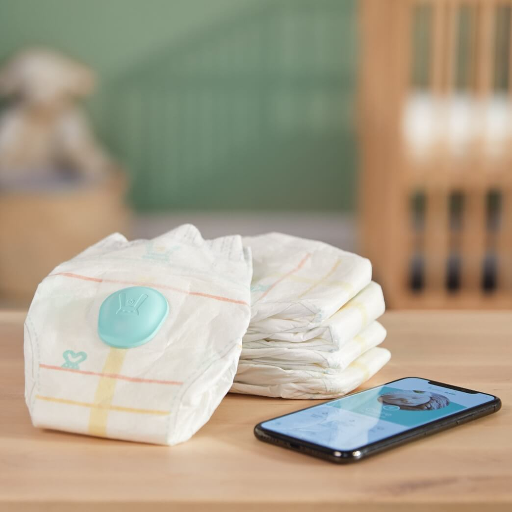 lumi by Pampers is a dirty diaper app that notifies parents when kids pants are dirty - shown are a stack of diapers next to a phone