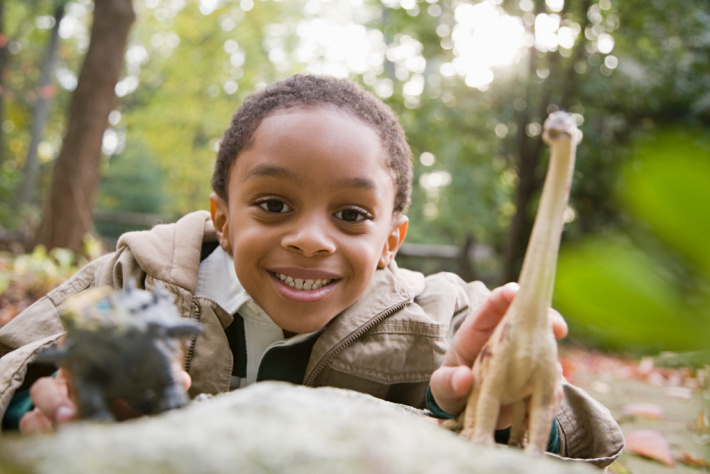 Kids Who Play with Dinosaurs are Smarter - Kids Activities Blog - boy playing with dinosaurs outside