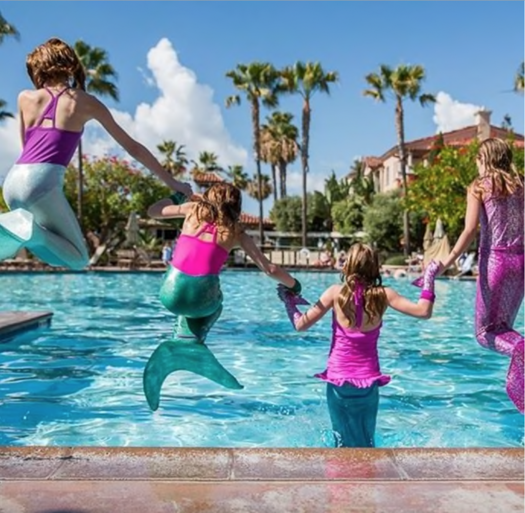 4 kids jumping into the pool wearing fabric mermaid tails for kids