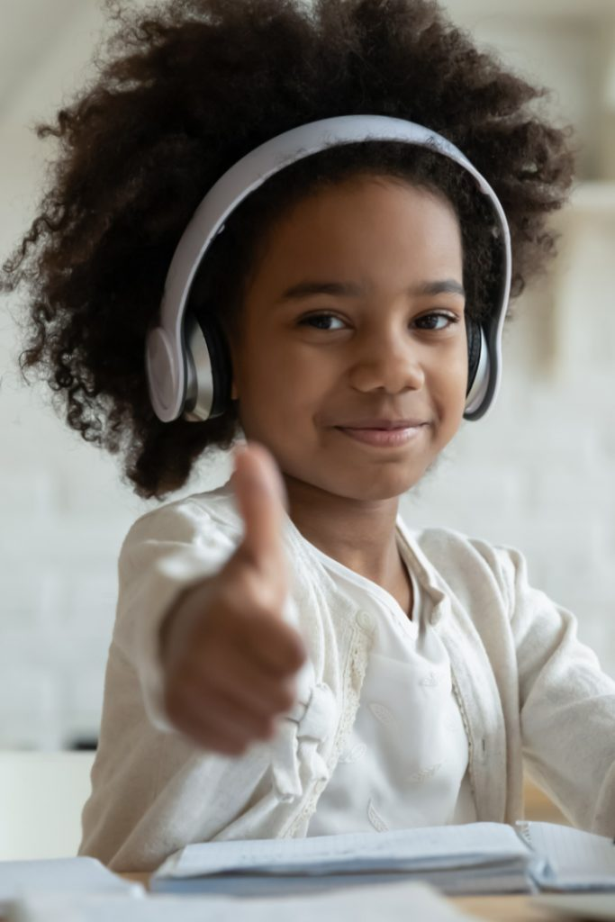 Free Educational Websites and companies offering kid lesson plans for home - Kids Activities Blog - child with headset in front of computer learning with free resource