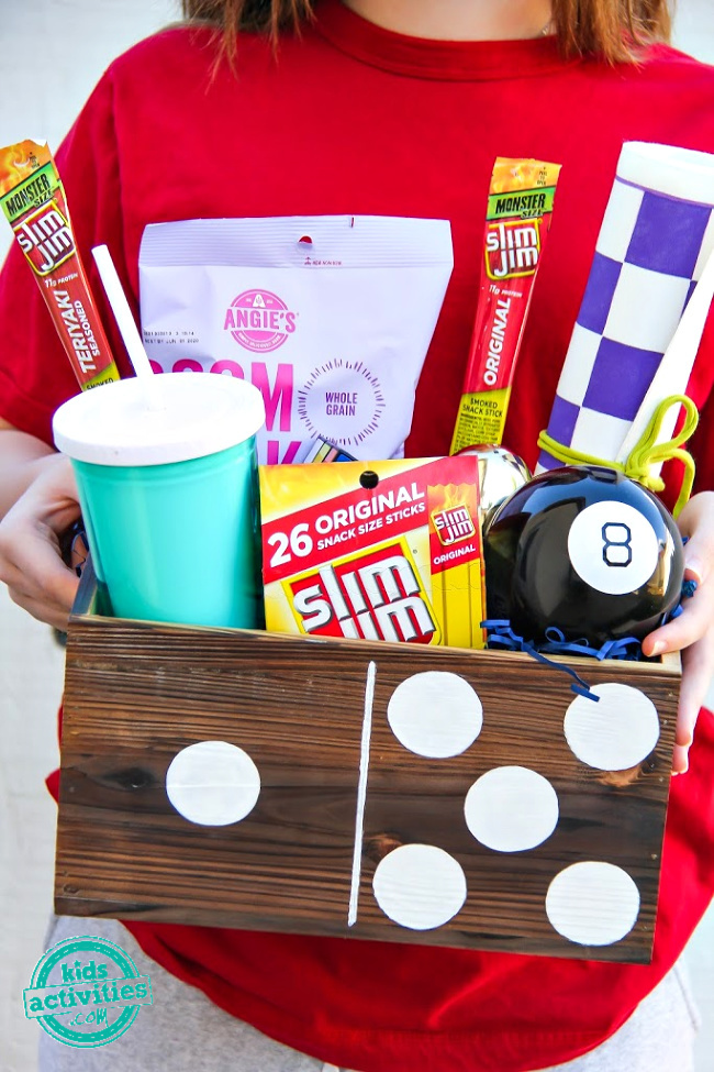 girl holding a game box filled with snacks and activities