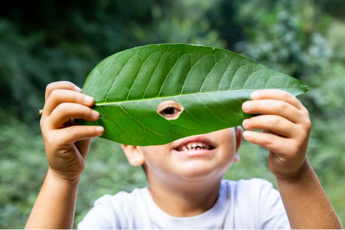 Kids spending time outside are happier - Kids Activities blog - child looking through a leaf