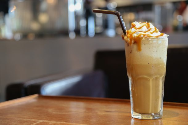 caramel iced coffee with whipped cream, caramel drizzle and straw
