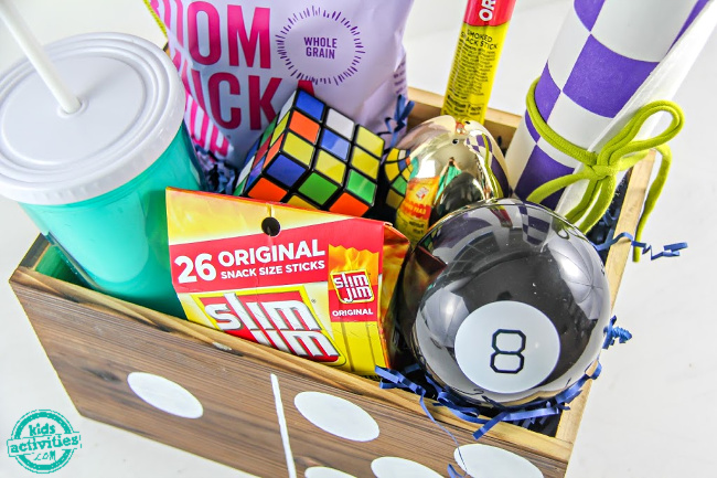 dominoes box filled with snacks and activities for kids