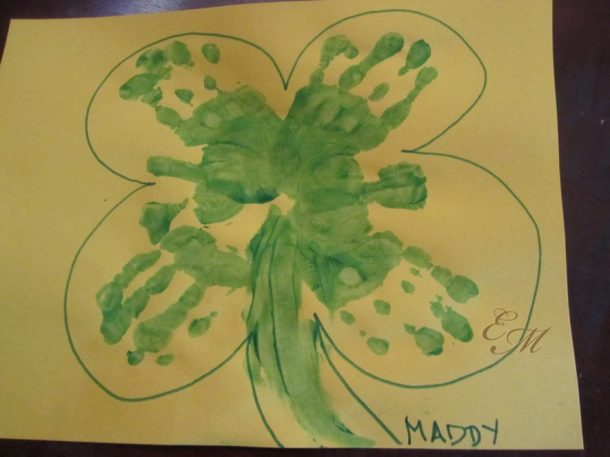 handprint 4 leaf clover made with green paint, with an outline drawn around it, on yellow paper.
