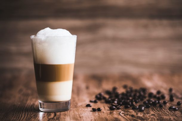 layered coffee with condensed milk, coffee, and foam in a tall glass on a wood table with coffee beans next to it