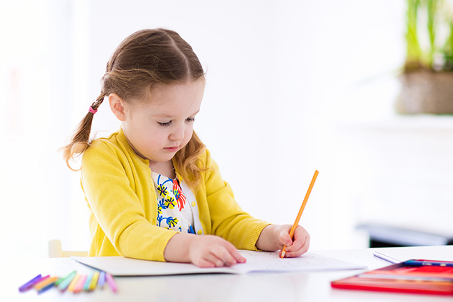 learn the letter a - preschool age girl writing in notebook