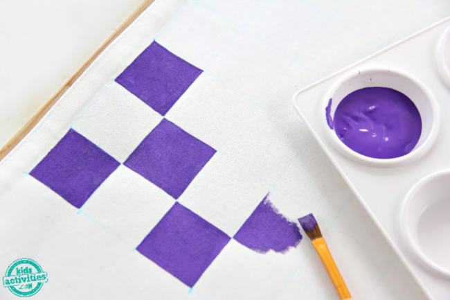 purple checks being painted on white fabric