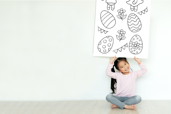 Coloring the really big coloring page mural - Kids Activities Blog - girl holding Easter poster size coloring page