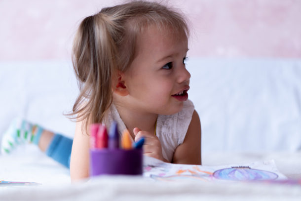 The Letter N Activities for kindergarten and below - preschool age girl on bed with worksheets and crayons
