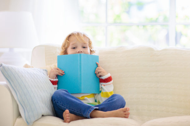 Letter M Activities - preschool age child sitting on couch with a book reading