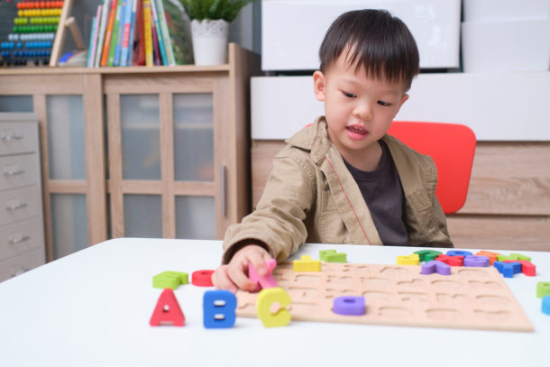 Words that start with F - preschool boy using alphabet shapes to learn the letter F