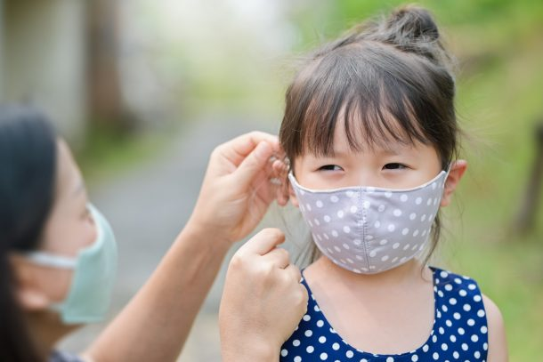 mother puts mask on daughter during coronavirus