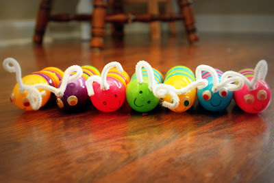 Plastic eggs that have been turned into caterpillars with faces and antennas.