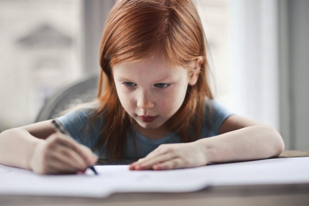 A little redhead girl is writing down all the things she wants to do this summer with a crayon.