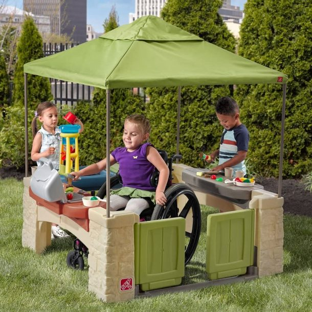 Step 2 outdoor playhouse has a wheelchair accessible design - kids playing together in the playhouse in backyard