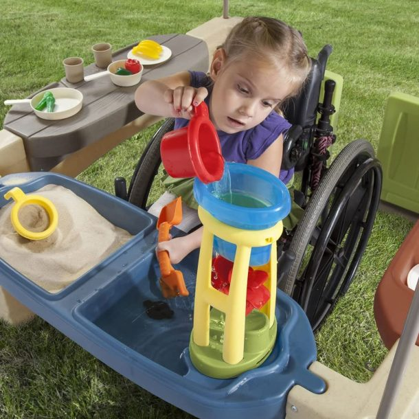 Wheelchair accessible outdoor playhouse design from Step 2 - girl sitting in wheelchair using water play and sand area