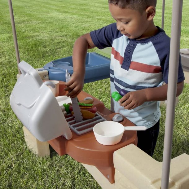 boy using the outdoor playhouse grill for pretend play