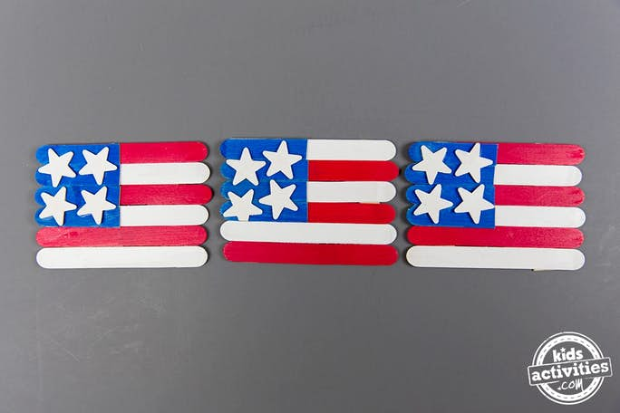 American Flag Craft for Kids perfect for Memorial Day - Kids Activities Blog - three popsicle stick USA flag crafts on gray background
