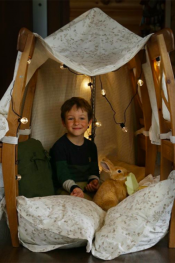 indoor blanket fort with dining chairs