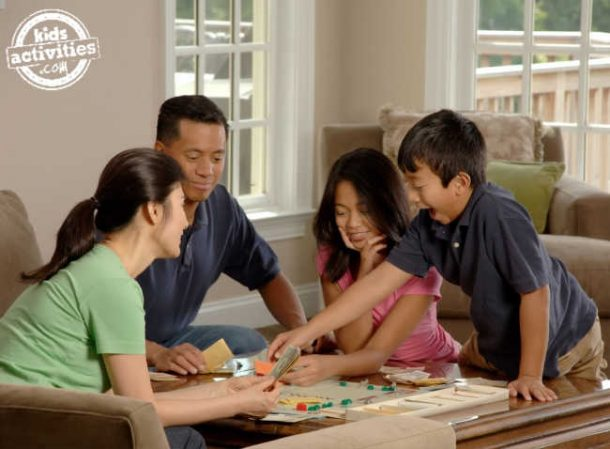 A family of four who are laughing sit at a table playing a board game.