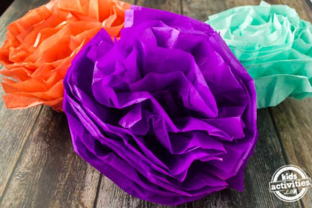 Colorful tissue paper pom poms displayed on a wood surface for cinco de mayo decorations