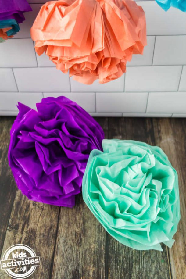 A orange mexican paper flowers is hanged for display while other mexcian paper flowers are displayed on the wood surafce below.
