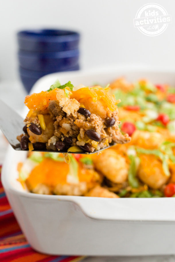 A ready-to-serve slice of taco tater tot casserole, just cut from a white 9x13 pan.